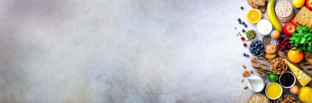Healthy breakfast ingredients, food frame. Granola, egg, nuts, fruits, berries, toast, milk, yogurt, orange juice, cheese, banana, apple on light grey concrete background, top view, copy space. Banner