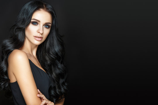 Beautiful woman portrait on black background. Glamour make up and long curly hair.