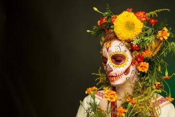 Женщина с разрисованным лицом к мексиканскому Дню Мертвых с цветами на темном фоне.