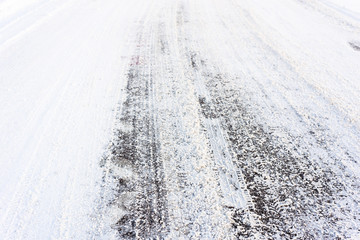 Country road in winter , asphalt covered snow with tire tracks, transportation concept