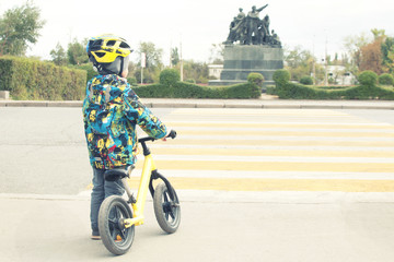 A boy with a bicycle crosses a pedestrian crossing with yellow markings