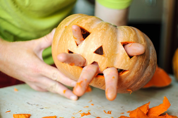Process of making Jack-o-lantern. Funny picture of Halloween pumpkin monster face with male fingers.