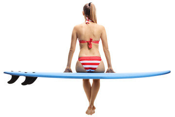 Young woman in bikini sitting on a surfboard