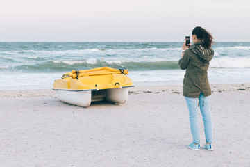 Woman takes a picture of a boat on her mobile phone