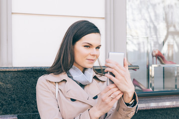 Young woman in a beige coat takes pictures of herself