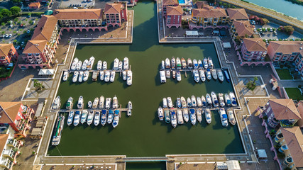 Aerial view of marina with boats and yachts on port of modern residential district from above
