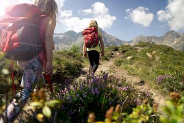 Kinder wandern mit Rucksack im Gebirge.
