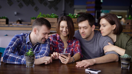 A company of friends who sit in a restaurant and wait for their meals, look with joy and laugh at photos on the mobile phone that were made during the holiday