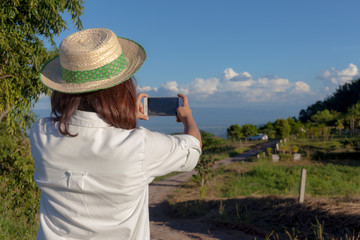 Beautiful young woman takes the mountain view on a mobile phone Landscape. At Khao Kho, Thailand.