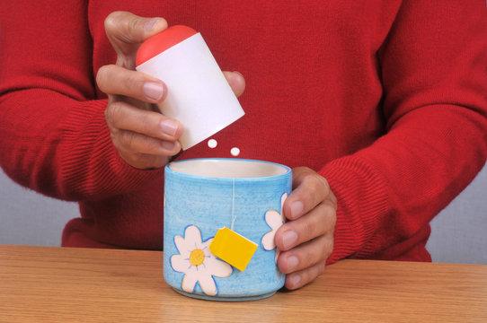 Personne mettant des sucrettes dans sa tasse de thé