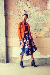 Young African American Woman wearing fashionable orange red jacket, dark red under top, dark blue flower patterned skirt, black boot shoes, standing by painted wall on street in New York, looking away