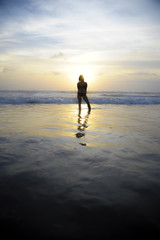 young woman on sea landscape sunset horizon with amazing sun and dramatic orange sky