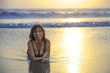 young Asian woman lying on wet sand on sea landscape sunset horizon with amazing sun