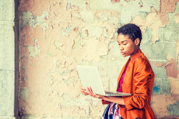 Young African American Woman studying, working on laptop computer outside in New York, wearing fashionable orange red jacket, skit, hands holding laptop computer, standing by painted wall on street.