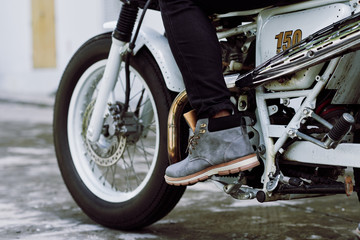 Close-up shot of male foot pressing gas pedal on vintage motorcycle, close-up shot