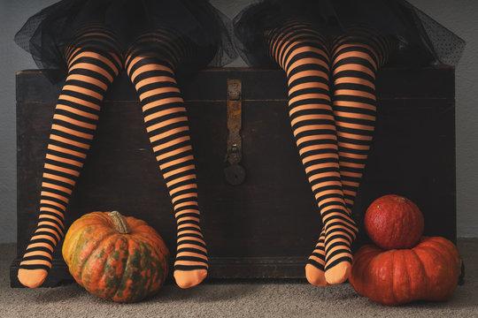 Happy halloween! Female feet in stockings with an orange pumpkin