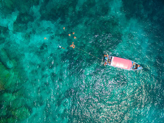 Aerial view of turquoise clear water, speedboat above coral reef, swimming and snorkeling people. Thailand.