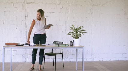 Wall Mural - Businesswoman with a tablet in her office, working.