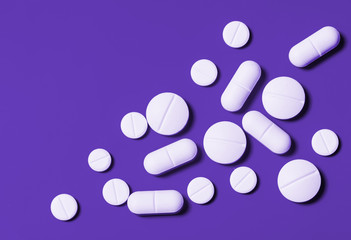 white tablets of various shapes on a bright purple background. Horizontal top view. Close-up