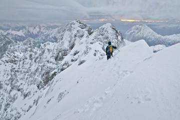 Bergsteiger klettert den Jubiläumsgrat im Winter bei Schnee von der Zugspitze zur Alpspitze