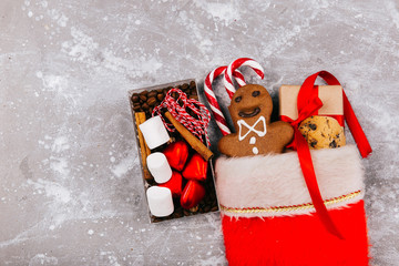 Red Christmas socks with cookies, ginger bread, red white cnadies and present box