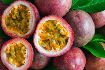 Fresh passion fruit on wood table in top view flat lay for background or wallpaper. Ripe passion fruit so delicious sweet and sour. Close up on a half of passion fruit in macro concept.Tropical fruit.