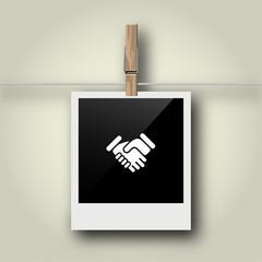 Sofortbild mit Symbol an Wäscheleine - Handschlag