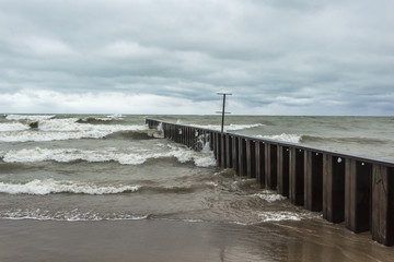 Divider leading out to lake as rough waves crash