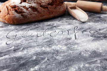 bread with flour and rolling pin on dark background