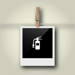 Sofortbild mit Symbol an Wäscheleine - Feuerlöscher