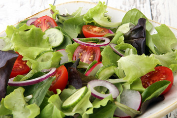bowl of salad with vegetables and greens, with tomato, cucumber and onions