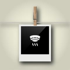 Sofortbild mit Symbol an Wäscheleine - Feuermelder