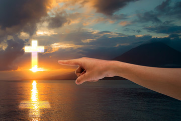 pointing towards the Christian cross in the sky