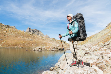 A hiker girl in sunglasses and a hat with a backpack and mountain gear with tracking treks in her hands looks at the beautiful view of a high mountain lake in an archipelago in the northern Caucasus