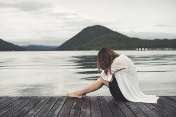 Lonely woman sitting on wooden pier and looking at the lake