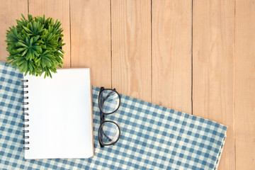 Top view empty book and eyeglasses and tree on table cloth over desk. copy space