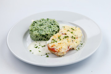 simple dish of Russian, Belarusian, Ukrainian cuisine on a white background chicken with cheese and rice and greens.