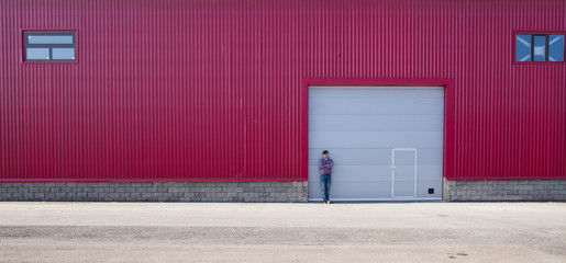 red metal warehouse with gates, the man near the garage