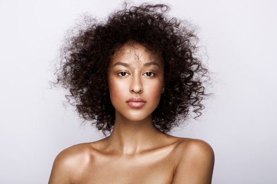 Fashion studio portrait of beautiful african american woman with perfect smooth glowing mulatto skin, nude make up