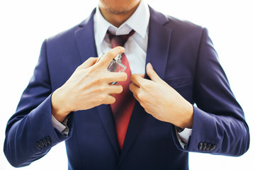 Metro-sexual man in formal suit applying perfume over white background