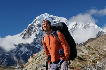 Улыбающийся турист с рюкзаком, стоит на фоне горы.