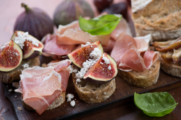 Photo sur Plexiglas Assortiment Close-up of bruschettas with prosciutto ham and ripe figs, selective focus