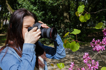 young woman takes pictures of nature near the lake