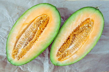 Melon on the wooden backround. Two parts a ripe green melon