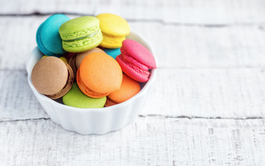 Aluminium Prints Macarons Vibrant colorfull macarons in plate on white wooden table. Text space