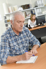 Senior office worker taking notes
