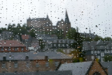 Stadtpanorama von Marburg/Lahn mit Schloss hinter einer Scheibe mit Wassertropfen, in denen sich die Gebäude spiegeln