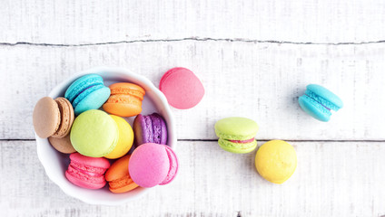Wall Murals Macarons Top view flat lay Vibrant colorfull macarons on white wooden table. Text space