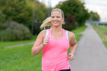 Blonde smiling woman running along river