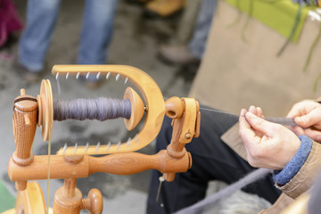 Master spinner spins yarn from wool on an old spinning loom